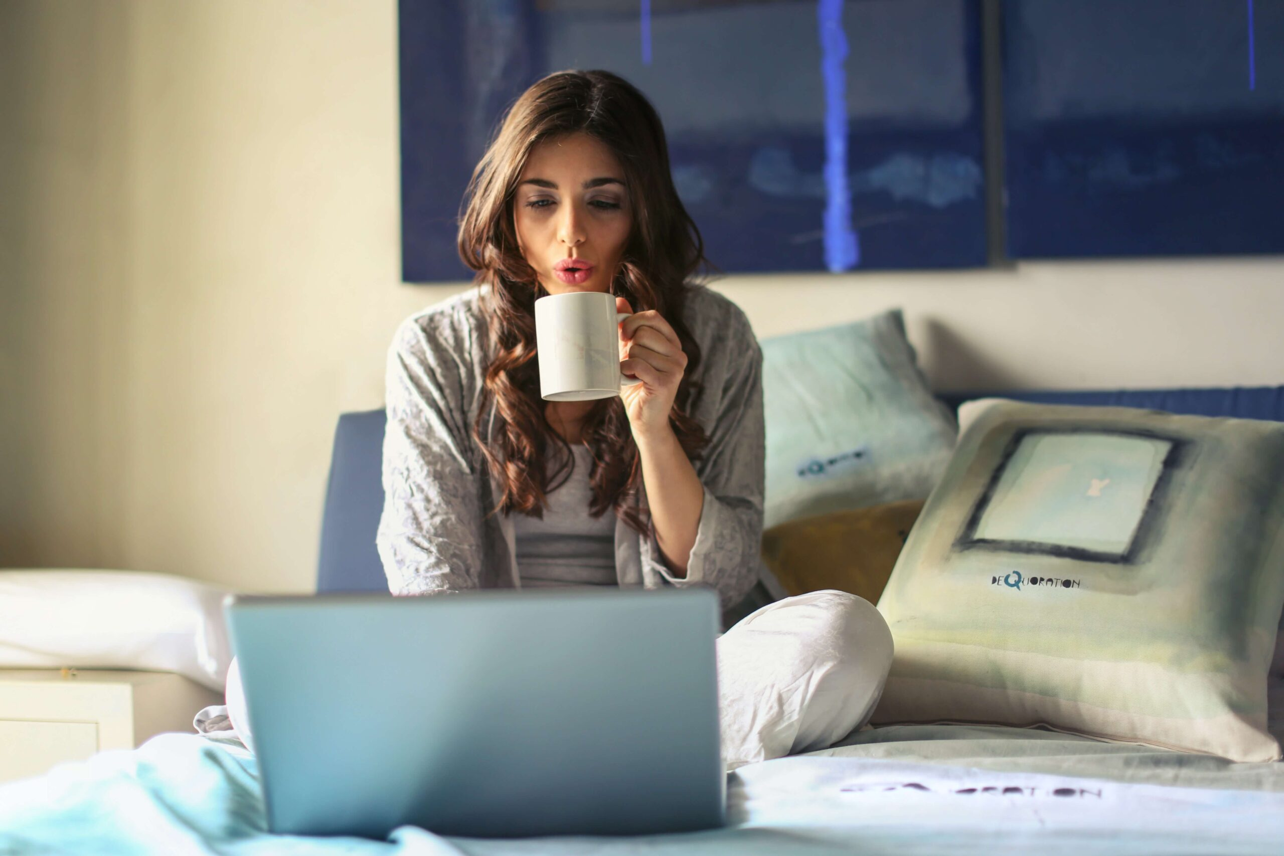 women drinking coffee whilst doing a side hustle on her laptop
